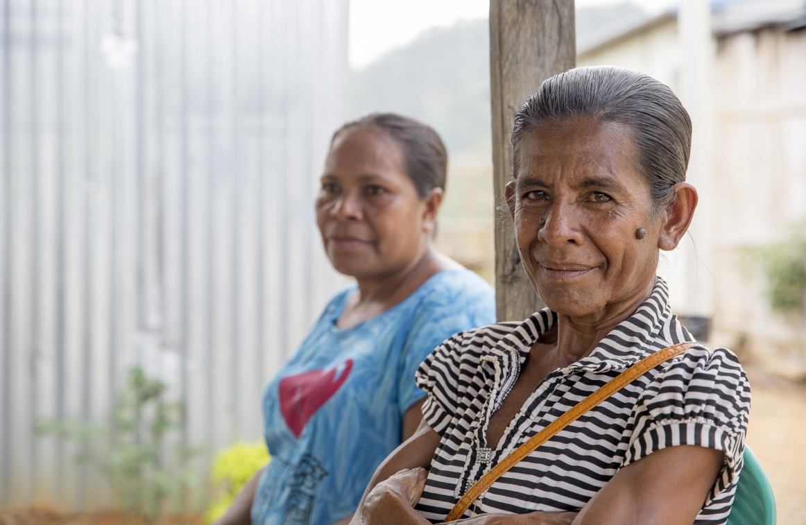 Image of two women in Timor sitting on a veranda. One of the women is staring straight at the camera and wears a stripy top.