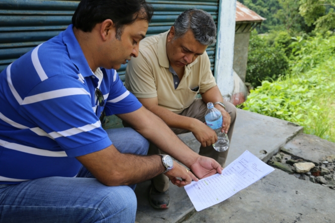 Image of two enumerators in Nepal discussing the IDM survey while sitting down outside.