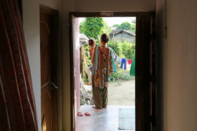 This image shows a woman standing in a doorway, with her back to the camera. She is holding a child on her hip and they are both looking out to the garden. This image illustrates a blog about Family Planning ahead of Women Deliver.