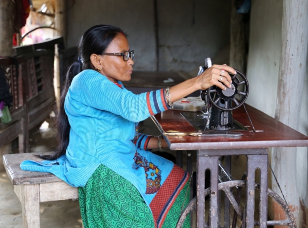 Image of a woman in Nepal sitting at a sewing machine. She wears a bright blue top and green pants and has her left hand on the sewing thread.