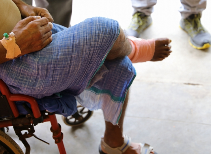 This photo shows a patient in a hospital in Nepal. He is sitting, with his leg crossed and an orange bandage around his right ankle. The photo does not show his face, but focusses on his legs. This image is used to illustrate this news item on Women Deliver and the IDM's health dimension