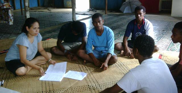 Image from initial research in Fiji, a woman enumerator is sitting on a flax mat with four young men discussing the research.
