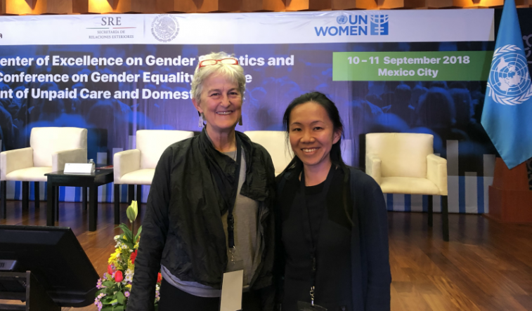 Photo of Dr Mandy Yap standing with Nancy Folbre, of the University of Massachusettes. They are standing in front of the CEGS stage in Mexico City.