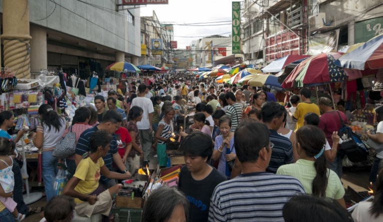 Image of a market scene in Manila. The street is full of people on foot buying from individual stalls under umbrellas.