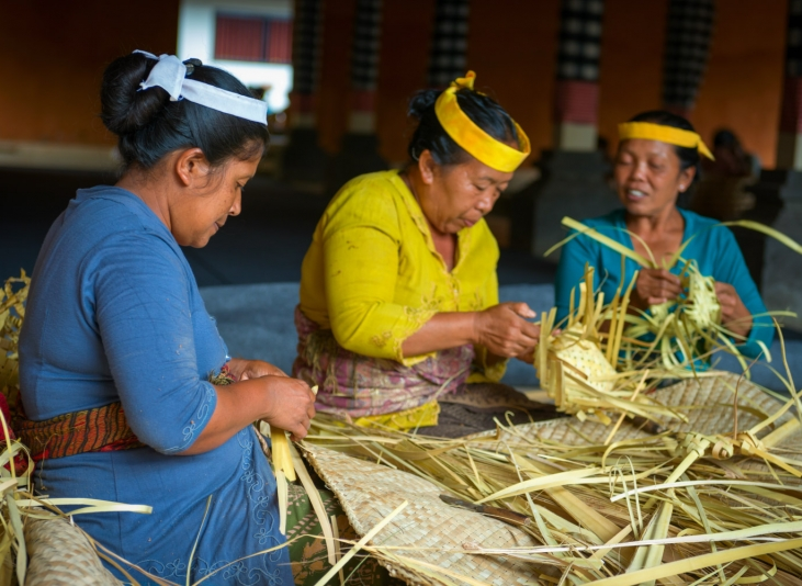 Image of three women sitting together, weaving in Indonesia.