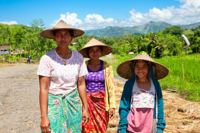 Image of three women in Indonesia standing next to a field. They have been farming for produce and are each wearing wide-brimmed hats.